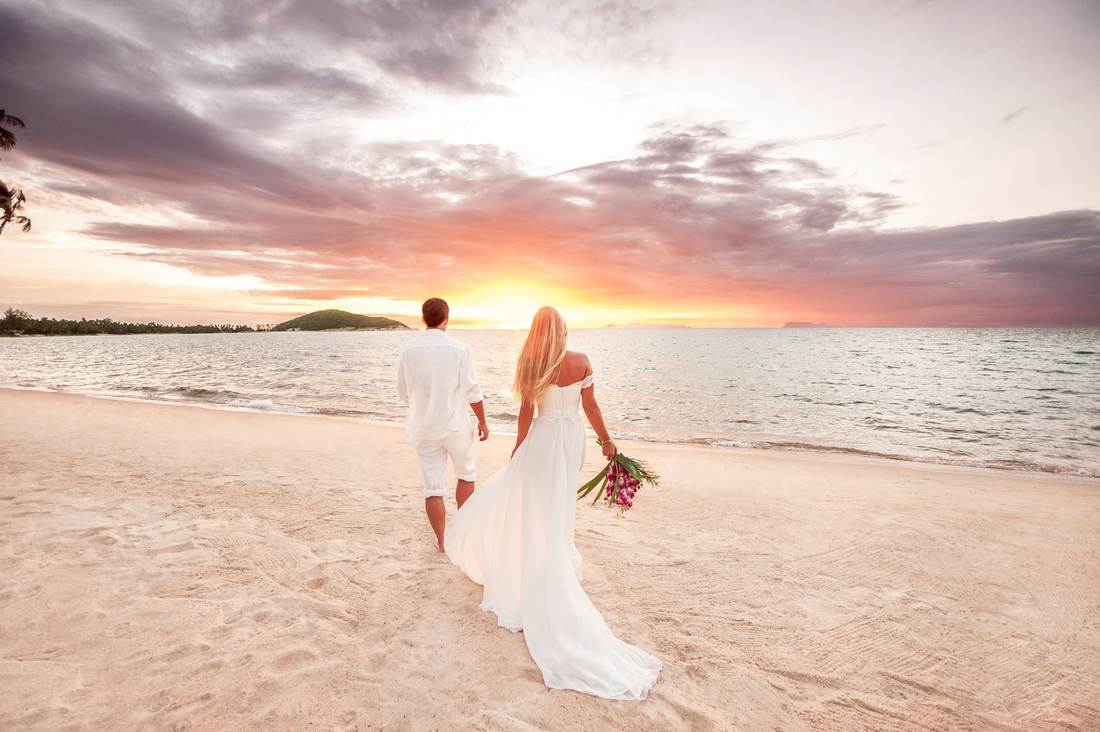 Bride following behind groom on beach